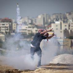 Un ragazzo palestinese lancia un lacrimogeno sparato dalla polizia israeliana durante una manifestazione per ricordare il primo anniversario della morte di Saji Darwish, un ragazzo ucciso dall'esercito israeliano