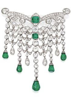 An Art Deco Platinum, Emerald and Diamond Devant de Corsage, France, Circa 1925. Designed as a graduated articulated swag supporting cabochon emerald drops, the top set with an emerald-cut emerald, and a square emerald-cut emerald, spaced by two old European-cut diamonds, set throughout with old European-, single-and rose-cut diamonds, French assay marks. #ArtDeco #corsage #brooch