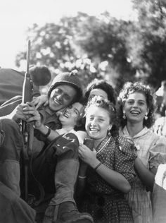 A group of French teenage girls hugs a soldier during the liberation of Paris, France, from German occupation during World War II. The soldier is smiling and holding his rifle. 25 Aug 1944 (Photo by RDA/Getty Images)
