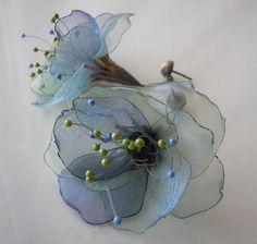 Kolczyki na sztyft, wykonane ze srebra i tkanin, w tym z przeźroczystej, mieniącej się organzy, wykończone dekoracyjnymi żyłkami nylonowymi. Tkanina oprawiona w srebro w formie dzwonka. Dostępne w kolorach: -błękit-szmaragd -czerwień-pomarańcz -złoto-brąz -błękit-fiolet Możliwość wykonania w innej kolorystyce na zamówienie. Wzór chroniony prawem autorskim.
