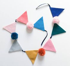A super lovely Pom-Pom flag bunting. It would look perfect hung up in your little persons nursery or playroom! Made from lovely shades of wool felt, I can also customise the colours, if you have any questions please send me a message! Approx size: 1 Metre in length - I can make the