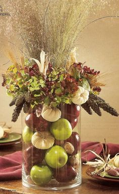 Fall decorating vase with filler and arrangement. I would substitute the grass for wheat, the rim with goldenrod hydrangeas and purple kale leaves, the red apples for pomegranates, use more walnuts and add orange pumpkins. But I like the design concept. ;-/