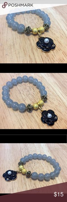 Clearance stretch charm bracelet Clearance item 💗💕. New without tags. Handmade on stretch cord and reinforced 3x for durability. Features 10mm light gray cracked glass beads and two 6mm gold stardust rounds. Also features two antique gold spacer beads. It is finished off with a black enamel inspired flower charm. Will fit a standard women's wrist handmade Jewelry Bracelets