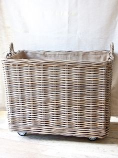 As featured in House Beautiful! Beautiful rattan basket on wheels with removable burlap lining30lx19wx25.5h handle