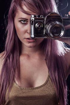 Portrait von Christina Key mit Lila Haaren und Kamera