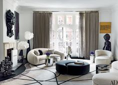 Decorator François Catroux furnished a London family's art-filled town-house, which was renovated by architectural designer Maha Kutay. In the living room, a Jean Royère sofa (at left) and a Vladimir Kagan sofa, lounge chair, and ottoman (all clad in sheepskin) mingle with Mauro Fabbro lamps from Alexandre Biaggi and a pair of custom-made interlocking ottomans | archdigest.com