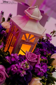 Illuminated lanterns paired with purple floral for a romantic reception centerpiece