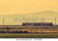 Old passenger train travelling in misty atumn morning through Brasov county, Romania. - stock photo