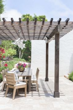 Alyssa Rosenheck - Amanda Barnes Interior Design - Amazing patio features a gray pergola accented with two Moravian Star Pendants which shades an outdoor dining space filled with a rectangular teak dining table and chairs.