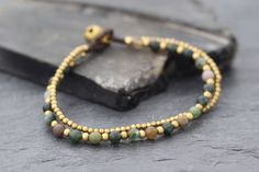 This is hand woven bracelet made with dark brown cotton waxed cord weaved together with fancy jasper stone and brass beads. Closure using brass bell