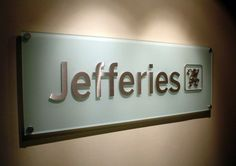 """Cut-out brushed aluminum letters 1/4"""" thick mounted onto top surface of frosted glass sign in NYC.  We specialize in custom aluminum signs  in New York, NY. Visit our website below to contact us for a free consultation! http://www.VisualSigns.com"""
