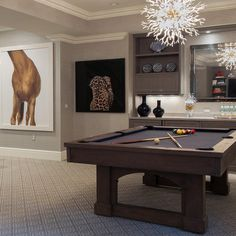 Gray basement game room features walls clad in grey grasscloth lined with a gray bar boasting gray cabinets facing a pool table illuminated by an Arteriors Diallo Small Chandelier.