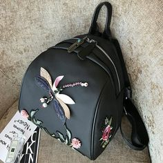 Жіночий міні рюкзак зі Стрекозою 🐝  Міні рюкзак виконаний з нейлону чорного кольору. Усередині рюкзака чорна підкладка. У головному відділенні одна кишеня на блискавці для дрібниць. Зовні на спинці розташована велика кишеня на блискавці. У цій моделі рюкзака є знімна плечова ручка 100 см завдовжки. Можна носити і як сумку і як рюкзак. Плечові лямки регулюються по висоті. Міні рюкзак прикрашений нашивками з квітів і Стрекози