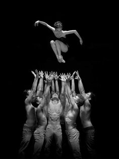 Ballerina floating above a group of male dancers