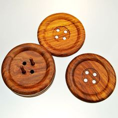Very unusual set of four coasters in the form of large buttons. Made from Sheesham wood by the versatile artisans of Noah's Ark in Moradabad, India, they are kept on a base with two vertical dowels that fit through the button holes. Coasters Diameter : 110mm Thickness : 14mm Holder Diameter : 113mm Height : 73mm