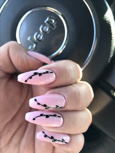 Pink coffin style nails with nail art, black stem with leaves