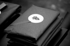Packaging Inspiration // Black paper with circular sticker with logo. Clean…