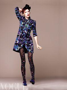 Coco Rocha-Dciembre Abrigo corto floral y zapatos con cordón de encaje, todo de Emporio Armani.