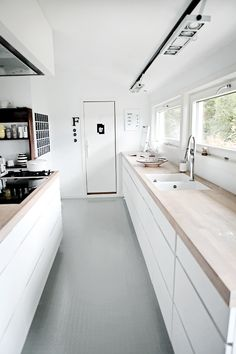 Love the grey rubber floor against the white units and wood work surface.