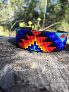 Beaded Cuff Bracelet in Light Red, Orange, Yellow and Blues on a Black Background. This Geometric Design Cuff is Handmade by the Artist. by PamBeadedAccessories on Etsy