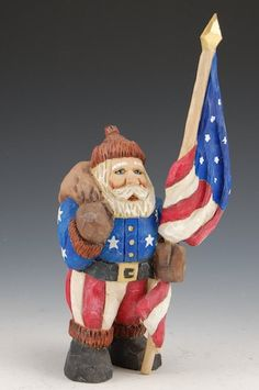 """""""Patriotic Santa Claus in red white and blue with white stars. Santa holds a toybag and a tall American flag. The flag does come apart in two pieces for safe shipping and storage. Both sections mount into Santa's hand. A hand crafted Santa Claus figure, carved from solid wood. Designed, carved by hand, painted, finished and signed by Russell Scott."""""""
