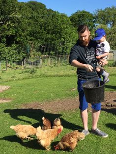Father Son feeding chickens Coombe Mill farm