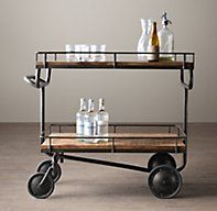 Warehouse Trolley Bar Cart - RH's Warehouse Trolley Bar Cart:Taking its design cue from a vintage factory trolley, our cart pays homage to the original's appealing balance of form and function. The handcrafted iron frame supports two wide wood-plank shelves, with gallery rails to keep items in place – from barware to books and collectibles. An integrated iron handle makes the cart simple to maneuver.