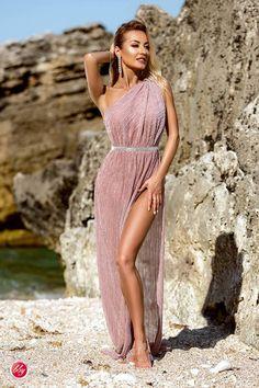 Vara adori rochiile lungi vaporoase, in stil roman. Afiseaza-te extravaganta intr-o rochie MAXI din voal lila plisat, prinsa pe un umar cu un accesoriu chic, cu talia accentuata si fusta lunga cu slit pe o parte si pantaloni scurti.