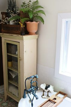 An antique cabinet serves as storage in the bathroom.