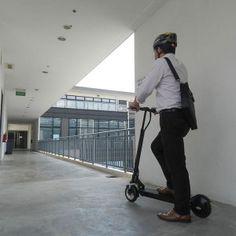 hombre de negocios con casco sobre scooter patinete electrico en pasillo