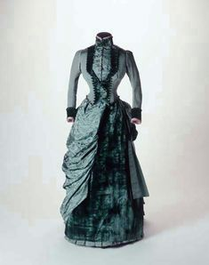 1884-1885 A two piece dress of petrol-blue ribbed silk, trimmed with blue glass buttons and blue velvet, worn at a wedding in 1885. It was made by Mrs. Christie who worked as a dressmaker from 8 Somerset Street, Portman Square, London. The bodice buttons at the front and has two small V-shaped tails at the back. -
