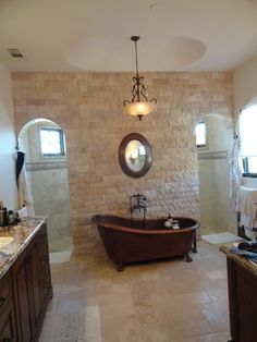 Master Bathroom- Nu-heat heated floors with chiseled edge travertine in Versaille pattern, back wall is split face travertine bricks. Copper slipper tub from Signature Hardware (great company) and walk through shower.