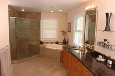 Remodeled bathroom featuring a drop-in oval bathtub in a corner deck by Neal's Design Remodel.