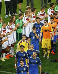 Germany's players applaud the Argentina team as they walk past to collect their medals after Germany won their 2014 World Cup final at the Maracana stadium in Rio de Janeiro July 13, 2014. REUTERS/Ricardo Moraes