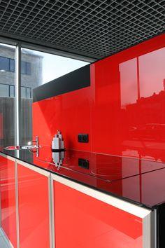 Rode glazen keukenachterwand gelakt op extra  helder glas. Te bekijken in onze toonzaal te Antwerpen.