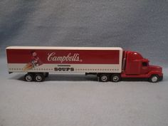 """This Ertl Diecast Campbell's Soup Freightliner Semi is 1/64th scale and measures 11 1/2"""" long x 2 1/2"""" high x 1 1/2"""" wide. Superior high gloss finish and nicely detailed graphics. Trailer rear lift up/slide in door opens & slides good, movable trailer stand works great and all chrome wheels & rubber tires on Cab & Trailer roll freely. Truck Cab & Trailer are in like new condition. No box with this one."""