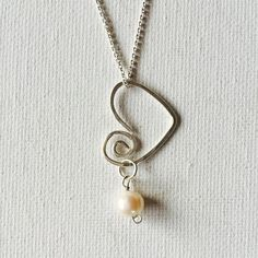 Made a Sterling silver spiral wire floating heart necklace with a white freshwater pearl!