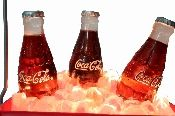 "Coca Cola Fountain. Vintage cooler with Coke bottles. The fountain is equipped with lights and the pump is in working order. The fountain measures 10"" to the top of the cooler's handle, 7"" across, and is 5 1/2"" deep. The fountain weighs approximately 13 lbs. and is highly collectible. The fountain is in mint condition."