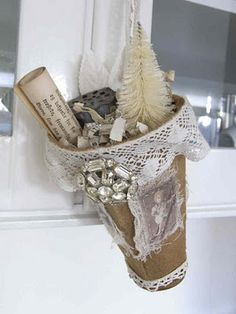 old worn fabric coffee filter with vintage lace, rhinestone jewelry pieces, cheesecloth, sweet images & a little wire handle.