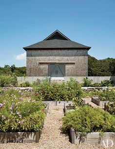 Next to the main barn, raised planting beds teem with vegetables, herbs, and flowers | archdigest.com