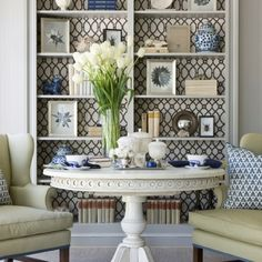 White table and wallpapered shelves