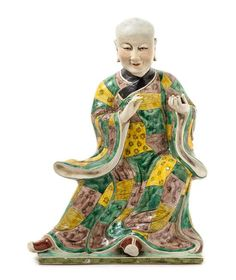 Chinese Famille Verte Porcelain Figure of a Luohan  20th century  the seated figure holding a small box in the left hand, wearing a long flowing robe of green, yellow and aubergine patchwork with a black collar.  Height 15 1/2 inches.