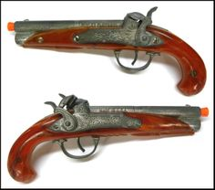 """Here's an original, 1950's vintage Hubley Flintlock, double-barreled pirate style cap pistol for you. This 9.25"""" pistol is very well-made of a heavy slush metal with a brown resin stock. The pistol is in excellent condition, as you can see in the photo. The trigger action works well. The fragile, resin grips are in excellent condition with no cracks, which is remarkable considering their age."""