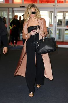 Khloé Kardashian wears a strapless jumpsuit and silk trench coat