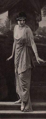 Les Modes (Paris) May 1913 robe du soir par Jenny robe du soir en broché jaune, jupe drapée, corsage en dentelle de Malines blanche. Plaque de broderie de perles et strass. Sous la dentelle, un ruban vieux bleu.