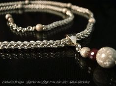 jens pind linkage sterling silver chainmaille necklace with a ruby and silv