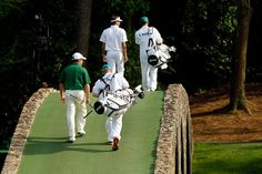 Bubba Watson of the United States and Louis Oosthuizen of South Africa walk over Hogan's Bridge with their caddies during the final round of the 2012 Masters Tournament at Augusta National Golf Club on April 8, 2012 in Augusta, Georgia.