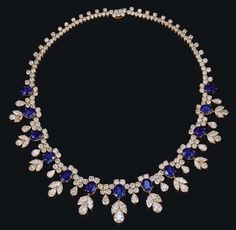 AN IMPRESSIVE DIAMOND AND SAPPHIRE NECKLACE, BY HARRY WINSTON    The front section set with thirteen graduated oval-cut or cushion-shaped sapphires suspending marquise-cut and pear-shaped diamonds, with pear-shaped and circular-cut diamond spacers, to the circular-cut diamond trefoil backchain, mounted in 18K gold, 40.0 cm.    Total weight of sapphires stated to be 35.29 carats; total weight of diamonds stated to be 46.19 carats    With jeweller's mark for Harry Winston