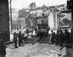 13.During the Battle of the Bulge, a U.S. Army half track crosses a temporary bridge over the Ourthe river, in the war-torn Belgian city of Houffalize, in January 1945
