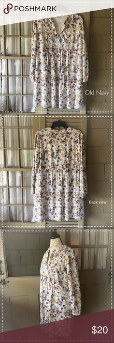 """Old Navy Floral Swing Dress Old Navy Floral Swing Dress. Size: L. Floral: Off White, Mustard, Black, Slate Blue, and Maroon. Body is lined, the only thing unlined are the sleeves. Shell: 100% Rayon/Viscose. Lining: 100% Polyester. Care: Machine wash gentle, line dry. Rounded split neckline. Long sleeve, slightly gathered and button cuffs. Pintuck pleats at front yoke. Seemed shirred back waist. Super soft mid-light weight. Only flaw is on the inside bottom hem material frayed about 1 1/4""""…"""